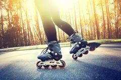 Adolescente en pcteres de ruedas en el verano Fotos de archivo