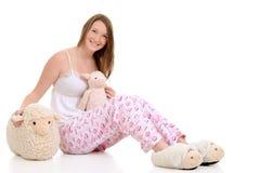 Adolescente en pijamas con las ovejas del juguete Fotos de archivo