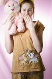 Adolescente en pijamas con un juguete suave Imagenes de archivo