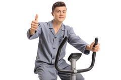 Adolescente en pijamas en una bicicleta estática que hace un pulgar encima de la muestra Fotos de archivo
