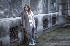 Adolescente en poncho en la calle Imagenes de archivo