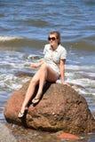Adolescente en roca en el océano Foto de archivo