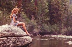 Adolescente en roca en el río Fotos de archivo libres de regalías