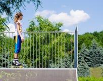 Adolescente en rollerblades en una rampa Fotos de archivo
