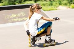 Adolescente en rollerblades que se agacha abajo Imágenes de archivo libres de regalías