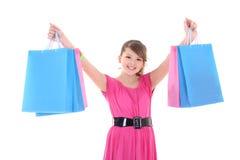 Adolescente en rosa con los bolsos de compras sobre blanco Imagenes de archivo