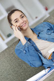 Adolescente en salón que habla con alguien en el teléfono móvil Fotos de archivo
