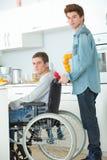 Adolescente en silla de ruedas y amigo Fotografía de archivo libre de regalías