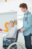 Adolescente en silla de ruedas y amigo Fotos de archivo