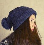 Adolescente en sombrero azul hecho punto con el pompom Fotos de archivo libres de regalías