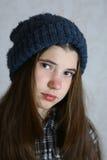 Adolescente en sombrero azul hecho punto con el pompom Imagenes de archivo