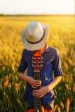 Adolescente en sombrero con la guitarra acústica Imagen de archivo libre de regalías