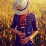 Adolescente en sombrero con la guitarra acústica, al aire libre Imagen de archivo