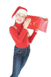 Adolescente en sombrero del ayudante de santa con el regalo Foto de archivo