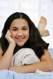 Adolescente en su cama Foto de archivo libre de regalías