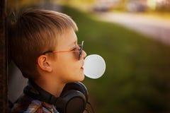 Adolescente en sunglusses con el chicle en puesta del sol del verano Fotografía de archivo