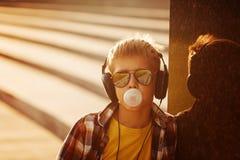 Adolescente en sunglusses y auricular con el chicle en puesta del sol del verano Foto de archivo