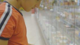 Adolescente en supermercado Muchacho adolescente caucásico en la camiseta roja que elige la mantequilla de la lechería del refrig almacen de metraje de vídeo