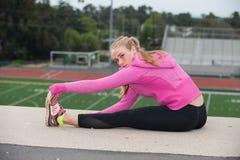 Adolescente en tendones de la corva que activan de la chaqueta rosada sobre campo Foto de archivo