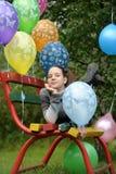 Adolescente en un banco con los globos Fotos de archivo libres de regalías