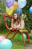 Adolescente en un banco con los globos Fotografía de archivo