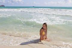 Adolescente en un bikiní amarillo en el océano Imagen de archivo
