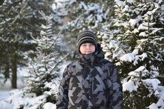 Adolescente en un bosque del pino en invierno Imagen de archivo