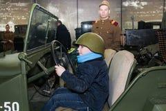 Adolescente en un casco en un coche militar Imagen de archivo
