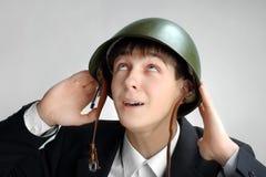 Adolescente en un casco militar Imagenes de archivo