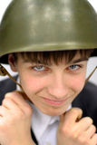 Adolescente en un casco militar Fotografía de archivo libre de regalías
