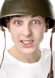 Adolescente en un casco militar Fotografía de archivo