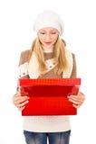 Adolescente en un casquillo del invierno con un regalo Imagen de archivo