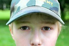 adolescente en un casquillo militar Fotos de archivo