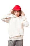 Adolescente en un casquillo y una ropa de deportes rojos Imagen de archivo