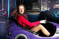 Adolescente en un coche de parachoques eléctrico Imagenes de archivo