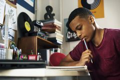 Adolescente en un dormitorio que hace el pensamiento del trabajo Imagen de archivo libre de regalías