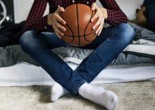 Adolescente en un dormitorio que lleva a cabo un concepto de la aspiración y de la soledad de la afición del baloncesto Fotografía de archivo libre de regalías