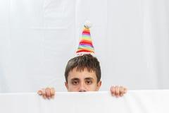 Adolescente en un fondo blanco que considera hacia fuera la mitad de la cara Foto de archivo