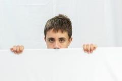 Adolescente en un fondo blanco que considera hacia fuera la mitad de la cara Imagen de archivo libre de regalías