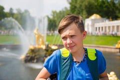 Adolescente en un fondo de la cascada magnífica en Peterhof Fotografía de archivo libre de regalías