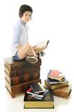 Adolescente en un montón de libros Foto de archivo
