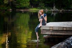 Adolescente en un muelle de la orilla del lago Fotos de archivo libres de regalías