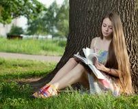 Adolescente en un parque con el cuaderno Foto de archivo
