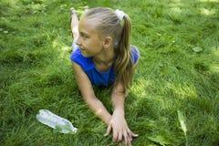 Adolescente en un parque que miente en hierba verde con la botella de wate Fotos de archivo libres de regalías