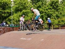 Adolescente en un salto de la bicicleta Imagenes de archivo
