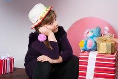 Adolescente en un sombrero con los regalos y los juguetes Imágenes de archivo libres de regalías