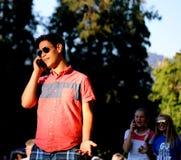 Adolescente en un teléfono celular con los espectadores Imagen de archivo