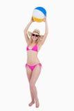Adolescente en un traje de baño rosado que aumenta una pelota de playa Imagen de archivo