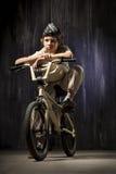 Adolescente en una bicicleta en un fondo de industrial Foto de archivo libre de regalías