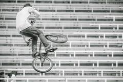 Adolescente en una bicicleta en un salto de altura Imagen de archivo libre de regalías